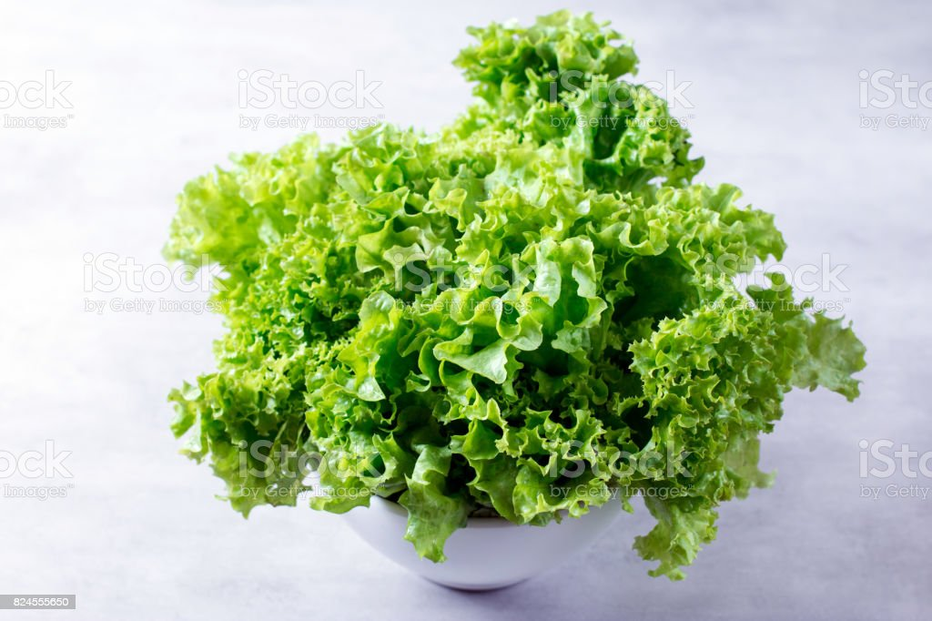 Salad leaves in a white bowl on the table stock photo