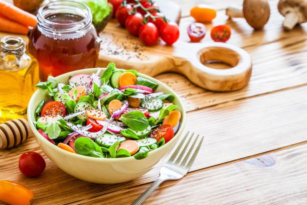 沙拉拌碗在木制野餐桌上拍攝 - 沙律碗 個照片及圖片檔