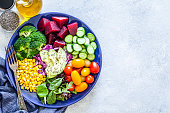 Top view of a blue salad plate filled with fresh organic colorful vegetables shot on light gray marble table. The composition is arranged at the left of an horizontal frame leaving useful copy space for text and/or logo. Vegetables included in the composition are tomatoes, cucumber, beet, broccoli, corn, avocado, arugula and lettuce. This ingredients are typical of the Mediterranean cuisine. Low key DSRL studio photo taken with Canon EOS 5D Mk II and Canon EF 100mm f/2.8L Macro IS USM.