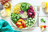 Top view of a blue salad plate filled with fresh organic colorful vegetables shot on light green picnic table. The plate is at the center of an horizontal frame with a fork beside it and is surrounded by some leaf vegetables, an olive oil bottle, a bowl with salad dressing, a bowl with chia seeds and a green textile napkin. Vegetables included in the composition are tomatoes, cucumber, beet, broccoli, corn, avocado, arugula and lettuce. This ingredients are typical of the Mediterranean cuisine. High key DSRL studio photo taken with Canon EOS 5D Mk II and Canon EF 100mm f/2.8L Macro IS USM.