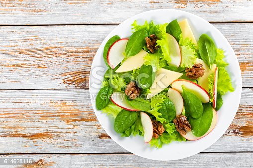istock salad of apple, spinach, cheese, lettuce leaves, caramelized wal 614628116