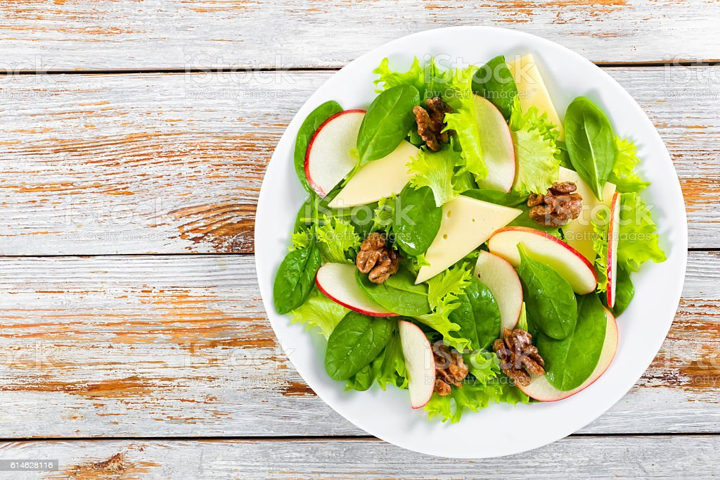 salad of apple, spinach, cheese, lettuce leaves, caramelized wal stock photo