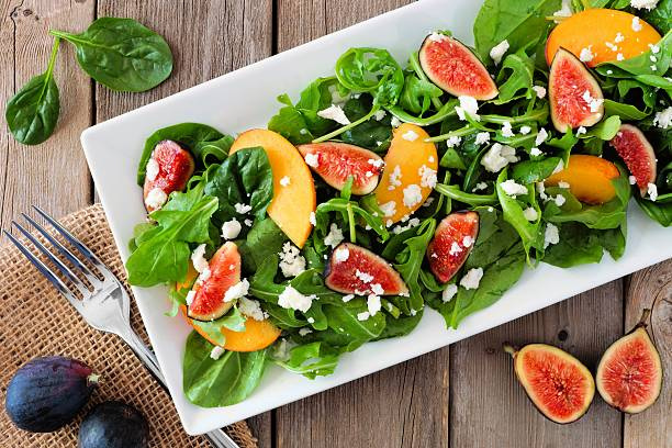 salad of arugula, spinach, figs and goat cheese, overhead scene - fig salad imagens e fotografias de stock