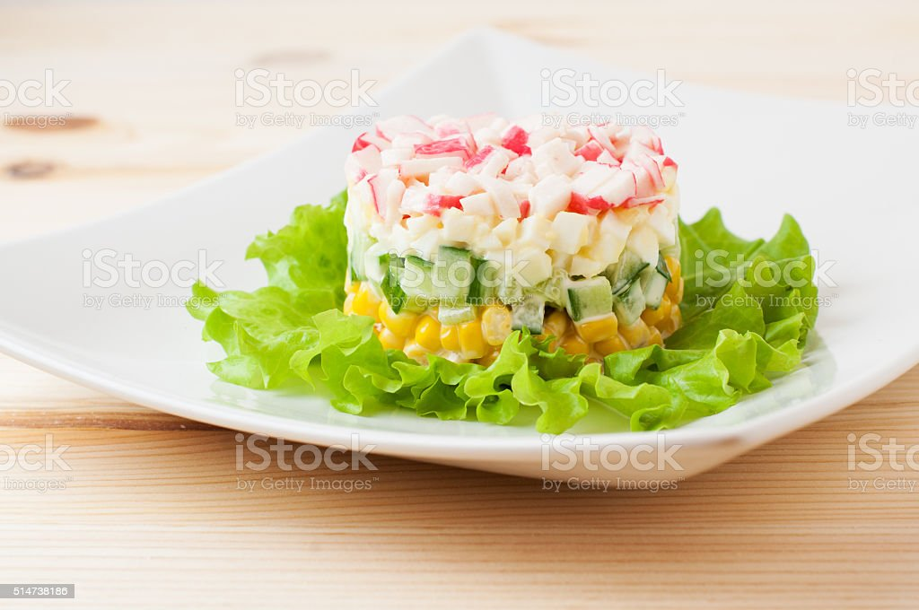 Salad of crab sticks on wooden countertop stock photo