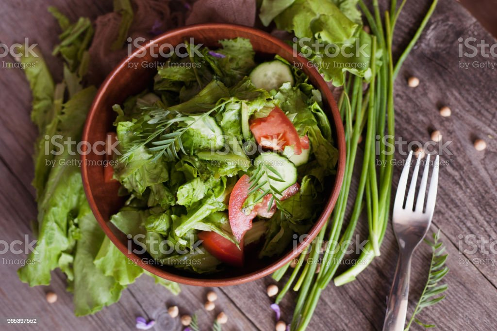 salad of fresh tomato, cucumber, lettuce and onion on a plate on a table royalty-free stock photo