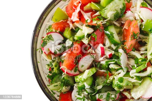 A cup with a salad of fresh vegetables isolated on a white background. View from above