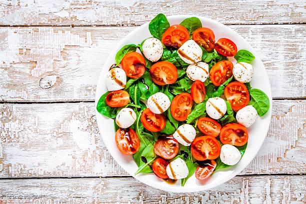salat mit mozzarella, kirschtomaten und spinat mit balsamico-sauce - caprese salat stock-fotos und bilder