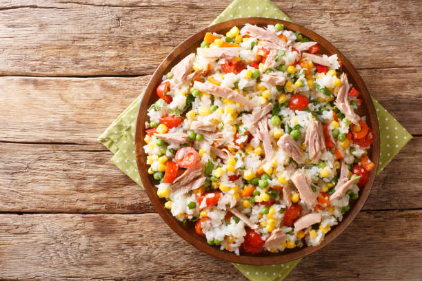 Salad of rice, tuna, tomatoes, sweet pepper, corn, green peas and herbs close-up in a plate. horizontal top view stock photo