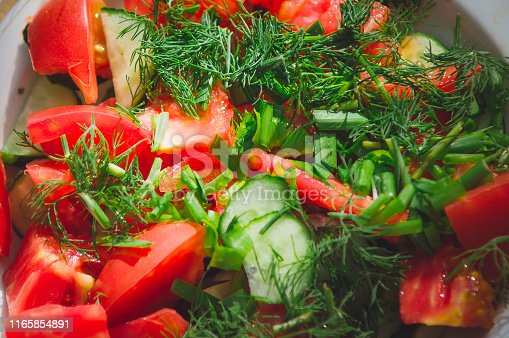 Salad of sliced tomatoes and cucumbers sprinkled with chopped herbs. Close-up, selective focus.