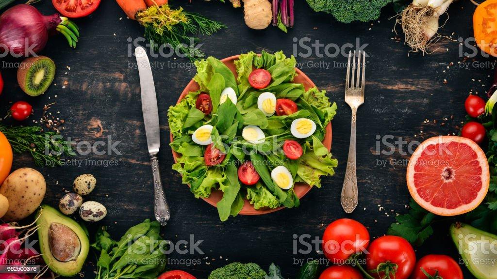 Salada de espinafre e codorna ovos em um fundo de madeira. Alimentação saudável. Vista superior. Copie o espaço. - Foto de stock de Abacate royalty-free