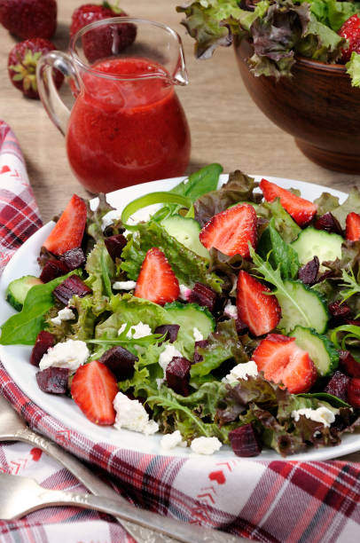 Salad of vinaigrette with strawberries Salad of vinaigrette with strawberries, tender feta and strawberry sauce. Vertical shot. vinaigrette dressing stock pictures, royalty-free photos & images