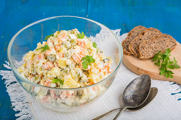 Salad olivier in bowl on blue table. Russian traditional salad. stock photo