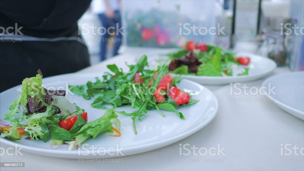 salad on a plate: arugula, iceberg, coriander, parsley, seafood and strawberries. Appetizing Dish in the restaurant. Salad preparation process stock photo