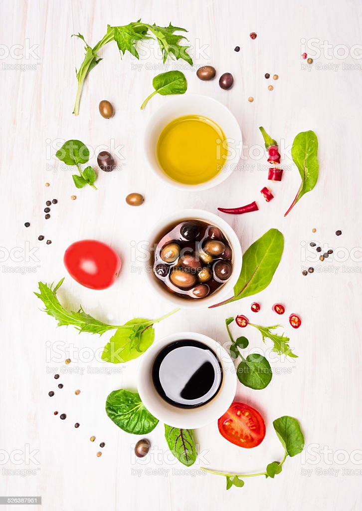 Salad preparation with dressings,olives, wild hebs ,  oil and tomatoes stock photo
