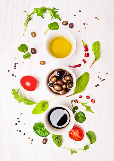Salad preparation with dressings,olives, wild hebs ,  oil and tomatoes Salad preparation with dressings,olives, wild hebs leaves, chili, oil and tomatoes on white wooden background, top view vinaigrette dressing stock pictures, royalty-free photos & images