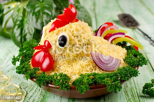 Salad shaped rooster on a plate on a wooden table. Attractive and fun food