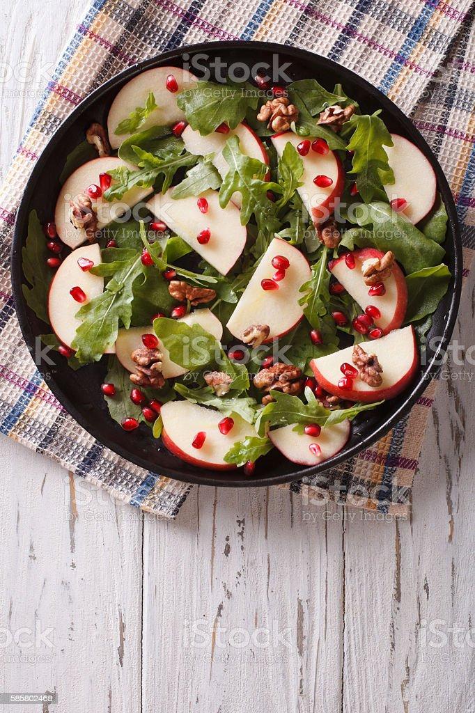 salad with apples, pomegranates, walnut and arugula. vertical stock photo