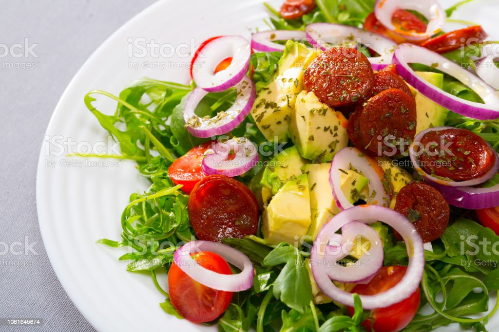 Salad with arugula and grilled sausages stock photo