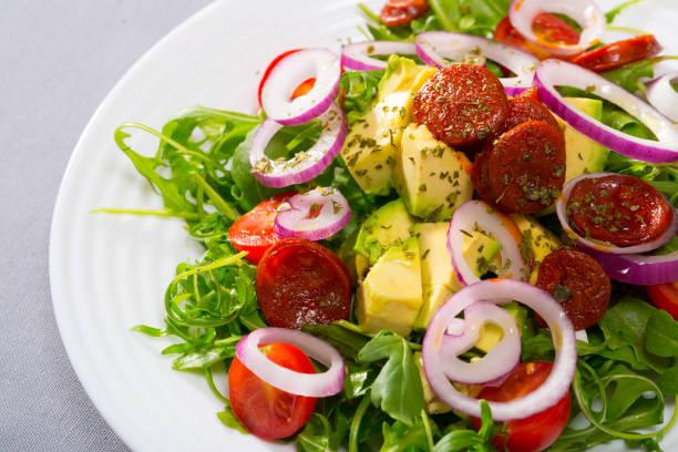 Salada com rúcula e as salsichas grelhadas - foto de acervo