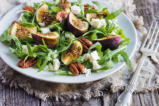 salad with arugula, figs, cheese and pecans stock photo