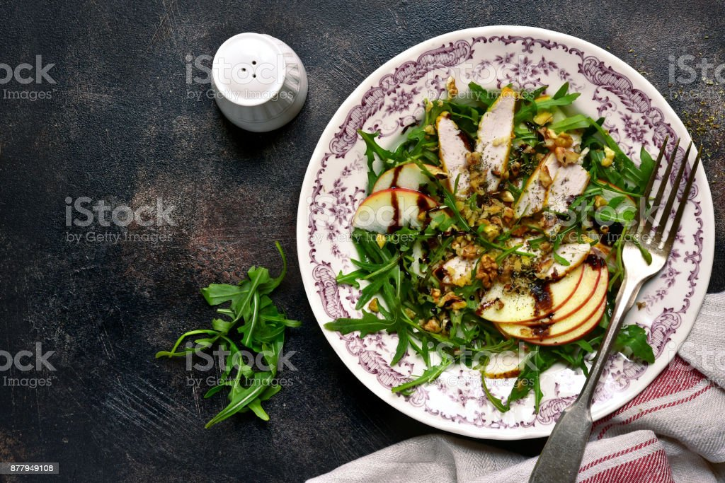 Salad with arugula leaves,roasted chicken,apple and walnut stock photo