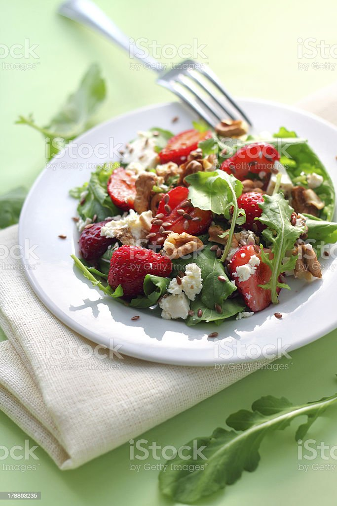 Salad with arugula, strawberries, goat cheese and walnuts royalty-free stock photo