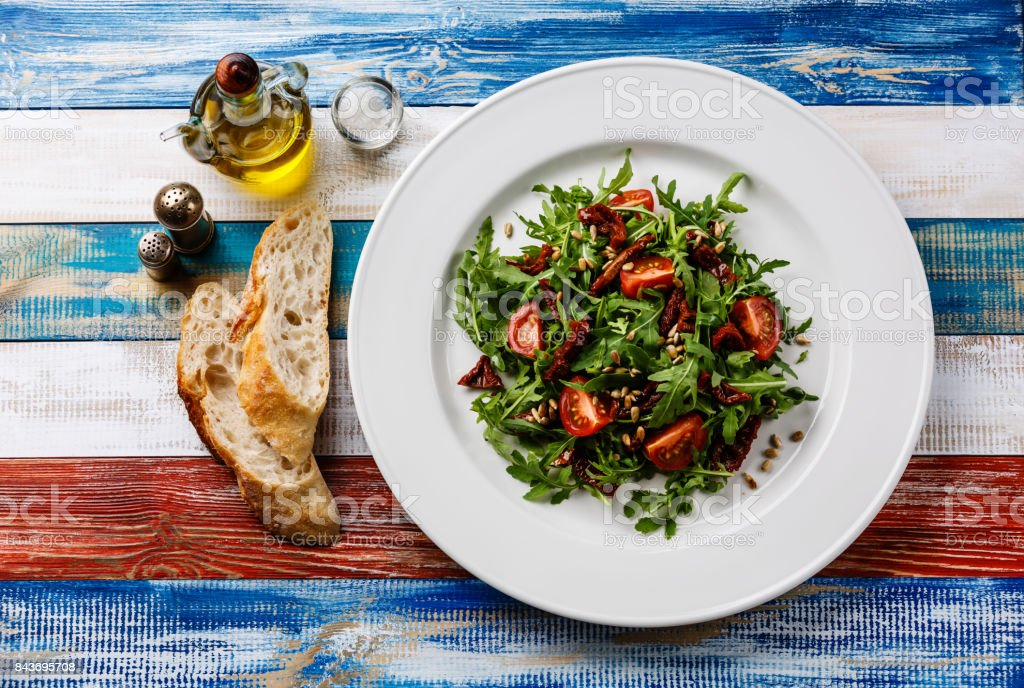 Salad with arugula, sun-dried tomatoes and sunflower seeds stock photo