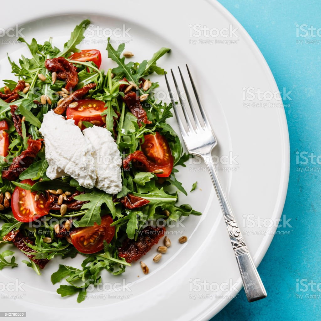 Salad with arugula, tomatoes and ricotta cheese stock photo