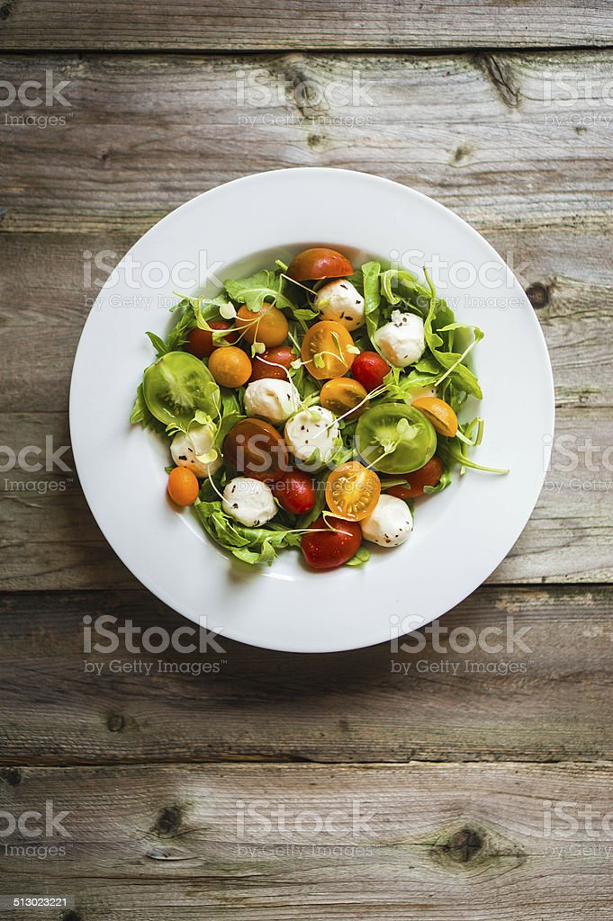 Salad with arugula,tomatoes and mozarella on wooden background stock photo