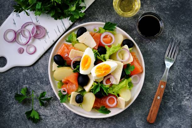 Salad with baby potatoes salted salmon, black olives, red onions, parmesan and lettuce. Organic healthy food. Top view. stock photo