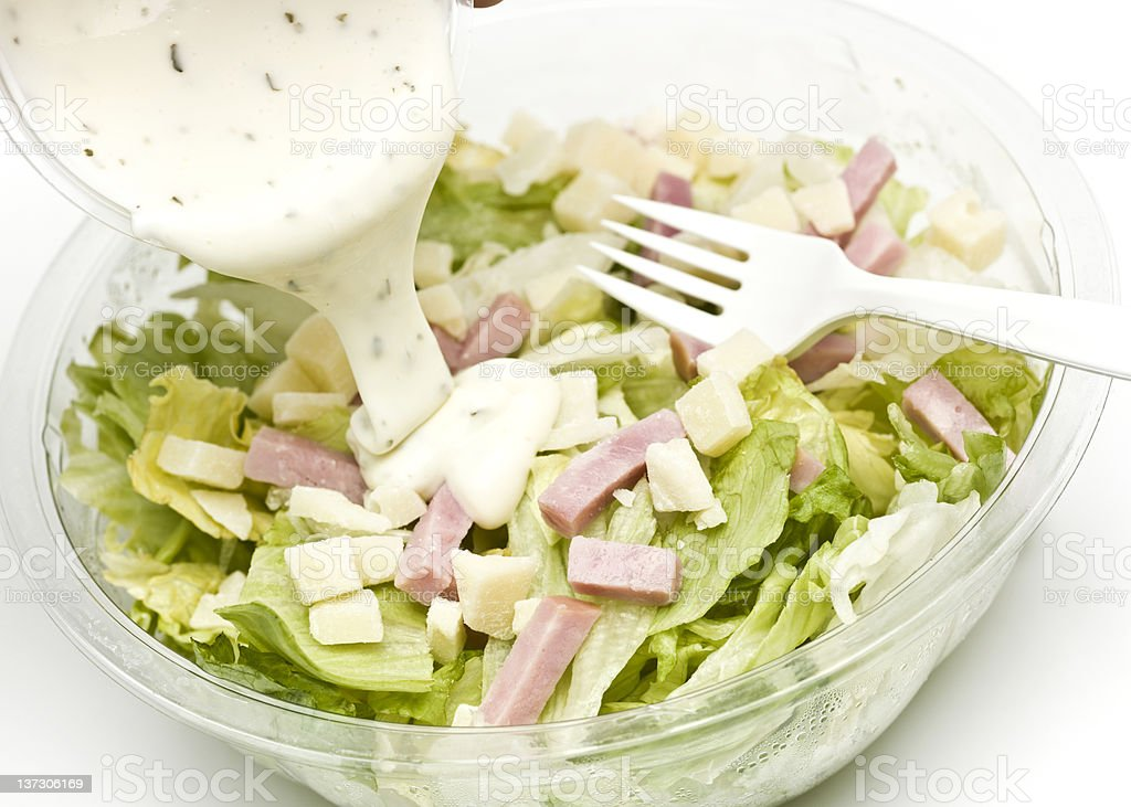 salad with bits of ham and dressing being poured over stock photo