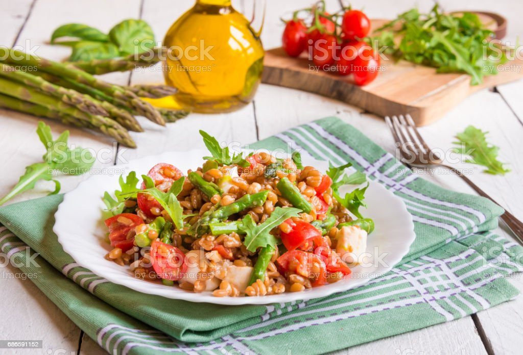 Salad with cereals, asparagus and tomatoes royalty-free stock photo
