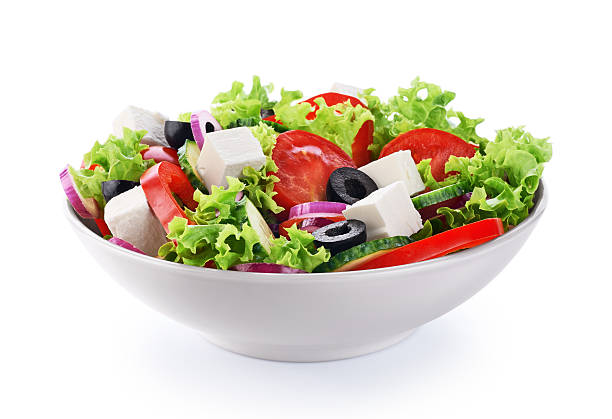 Salad with cheese and fresh vegetables isolated on white backgro stock photo