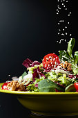 Salad with cherry tomatoes, walnuts and vegetable oil sprinkled with sesame.  Copy space.