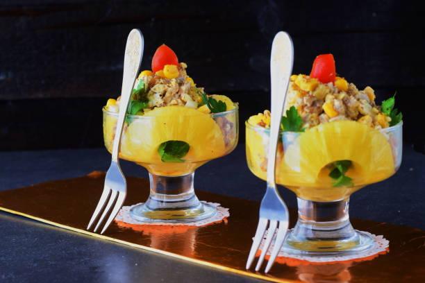 salat mit hähnchenfilet, ananas, pilze, abstrakte walnüsse in einer glasschale auf einem grauen hintergrund. gesunde ernährung-konzept. russische traditionelle speisen - ananas huhn salate stock-fotos und bilder