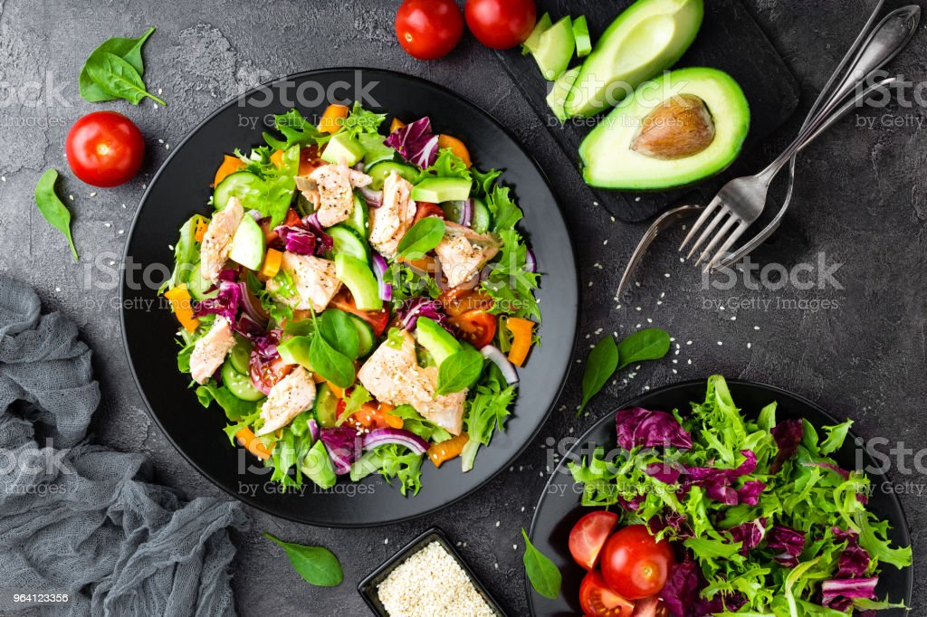 Salad with fish. Fresh vegetable salad with salmon fish fillet. Fish salad with salmon fillet and fresh vegetables on plate stock photo