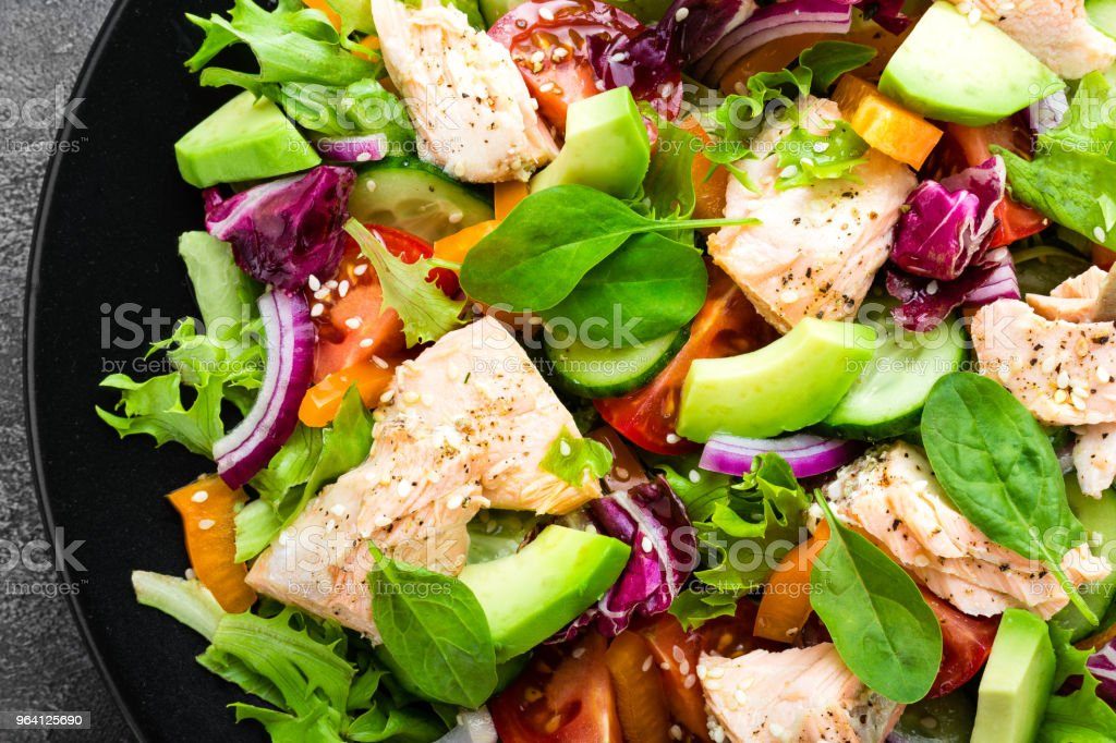 Salad with fish. Fresh vegetable salad with salmon fish fillet. Fish salad with salmon fillet and fresh vegetables on plate royalty-free stock photo