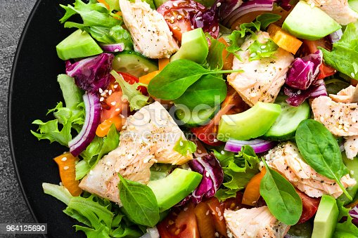istock Salad with fish. Fresh vegetable salad with salmon fish fillet. Fish salad with salmon fillet and fresh vegetables on plate 964125690
