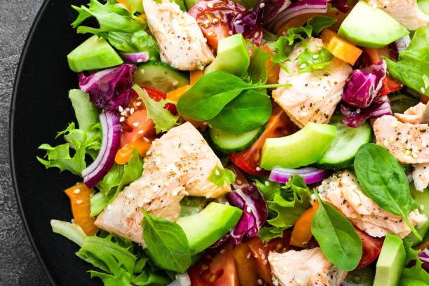 물고기와 샐러드입니다. 신선한 야채 샐러드와 연어 필렛 생선. 접시에 신선한 야채와 연어 필렛 생선 샐러드 - 점심 뉴스 사진 이미지