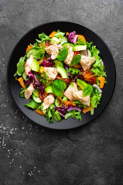 Salat mit Fisch. Salat aus frischem Gemüse mit Lachs Fisch Filet. Fischsalat mit Lachsfilet und frisches Gemüse auf Platte – Foto