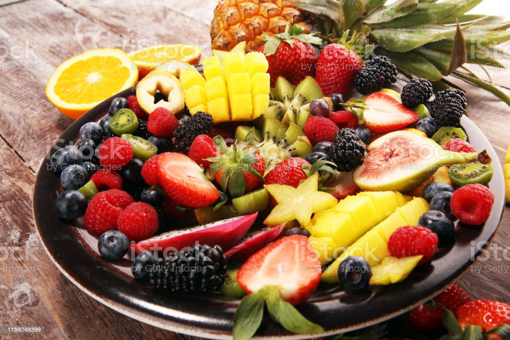 salad with fresh fruits and berries. healthy spring fruit salad on...