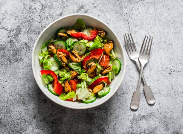Salat mit frischem Gemüse und Dosenmuscheln auf grauem Hintergrund, Ansicht von oben. Köstliche gesunde Ernährung – Foto