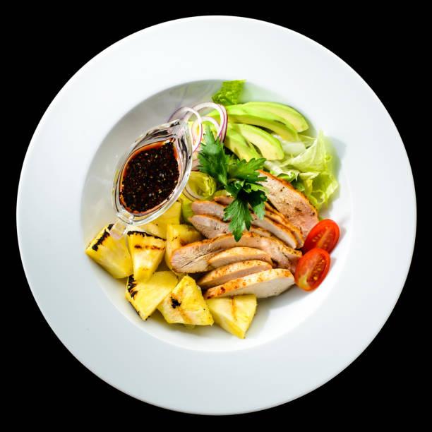 salat mit gegrilltem hähnchen und ananas in einem weißen teller-isolat - ananas huhn salate stock-fotos und bilder