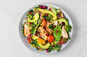 istock Salad with grilled chicken breast, avocado, pomegranate seeds and tomato on white background. Top view 1226733438