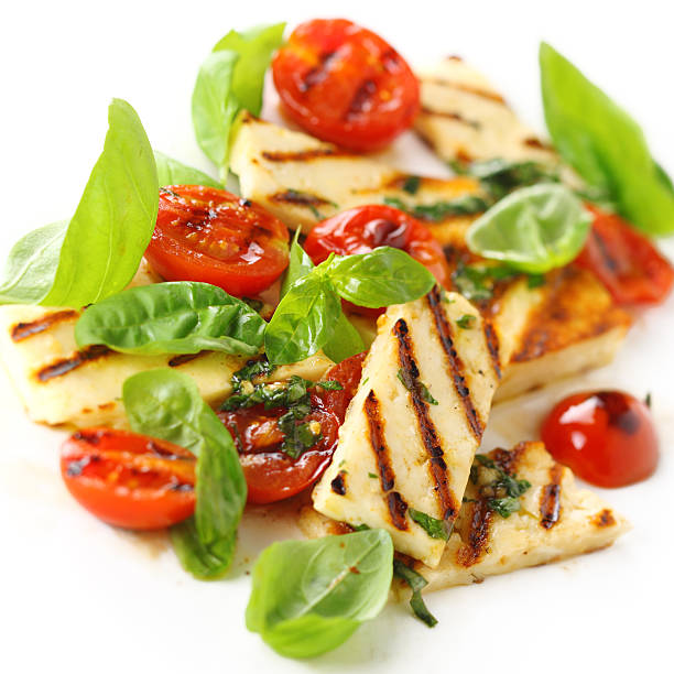 Salad with grilled halloumi cheese and roasted tomatoes stock photo