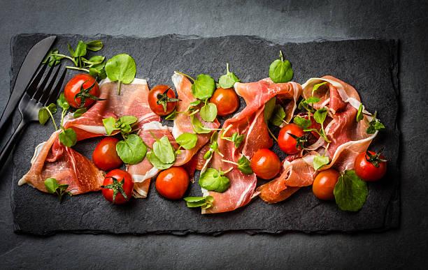 Salad with ham jamon serrano, cherry tomatoes, arugula, slate board stock photo