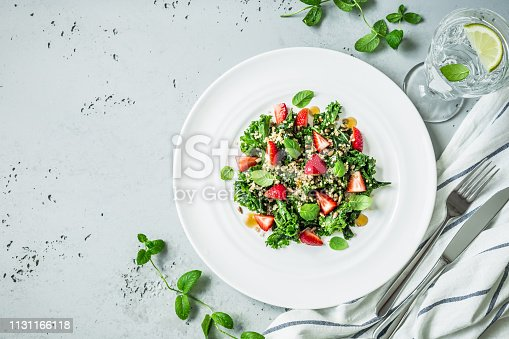 Fresh vegetarian salad with kale, strawberries, quinoa and mint leaves. White plate from above (top view, flat lay). Grey stone background. Layout with free text space.