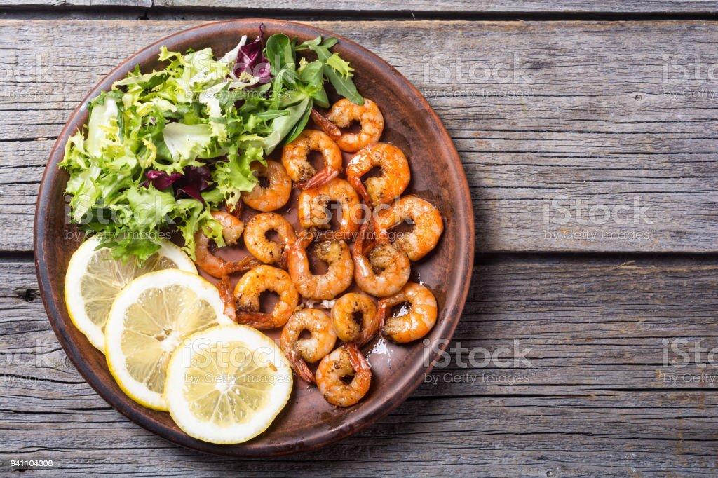 Salad with lattuce , lemon and shrimps stock photo