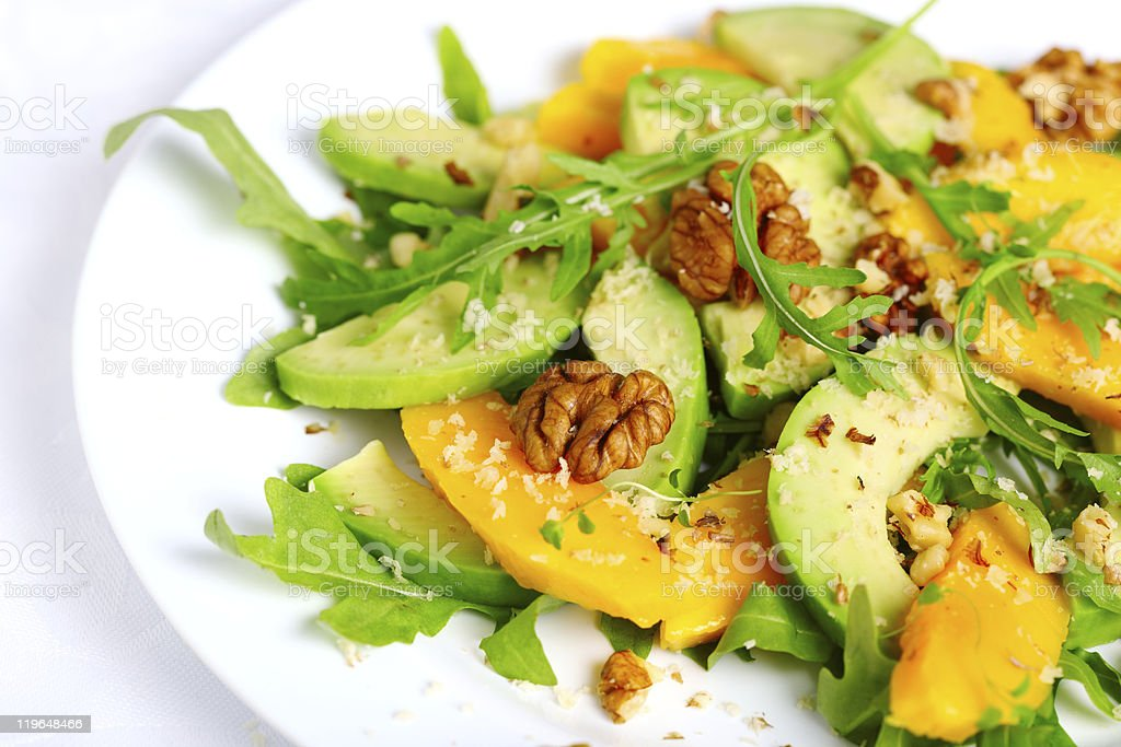 Salad with mango, avocado, arugula and walnuts stock photo