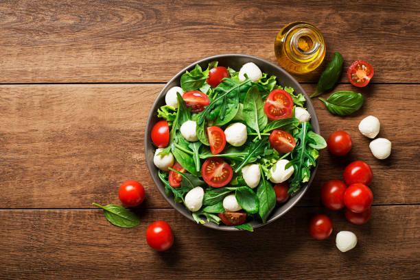 salat mit mozzarella, rucola und tomaten - caprese salat stock-fotos und bilder